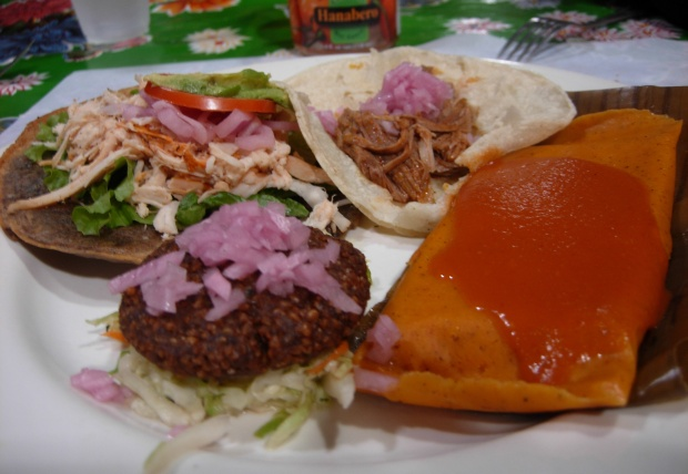 A plate of delights at Chichen Itza (clockwise from top left): panucho, cochinita pibil, chicken tamale, and kibi.
