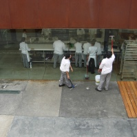 Students clean the windows of a classroom at the Tijuana Culinary Art School.