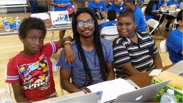 "DeCarlis Wilson, center, helps children learn to code at a ""hackathon"" organized by Teens Exploring Technology at the Nickerson Gardens housing project in Watts. (Daina Beth Solomon / Los Angeles Times)"